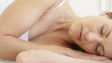 Beautiful brunette sleeping on her bed — Stock Video