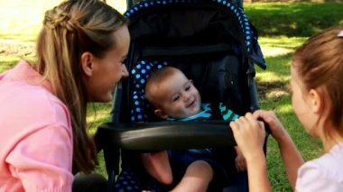 Mother and daughter playing with baby in a pram — Stock Video