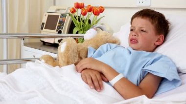 Little sick boy lying in bed with teddy bear — Stock Video