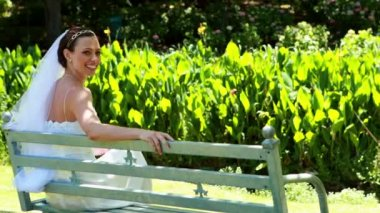 Beautiful bride sitting on bench — Stock Video
