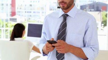 男子发短信的手机,而工作的同事在他身后 — 图库视频影像