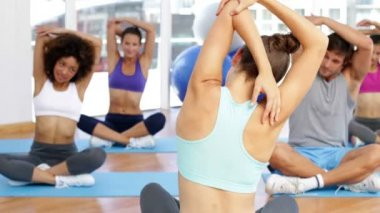 Fitness class sitting together and stretching — Vídeo de stock