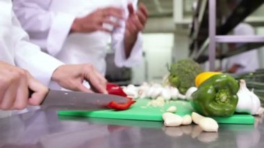 Chef slicing vegetables on a green board — Stock Video