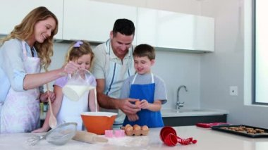 Happy young family making a cake together — Stock Video