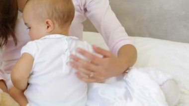 Mother playing with baby daughter on the bed — Stock Video