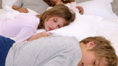 Cute parents and children lying on bed sleeping — Vidéo
