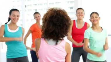 Pretty instructor leading zumba class in fitness studio — Vídeo de stock