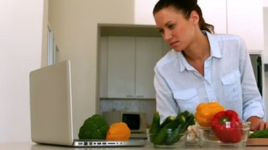 Woman following recipe on laptop — Stock Video