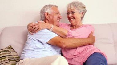 Senior couple sitting on sofa hugging — Stock Video