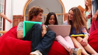 Happy classmates sitting on bean bags in common room — Stockvideo