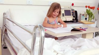 Little girl sitting in hospital bed colouring — Stock video