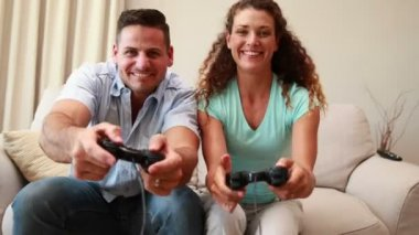 Young couple sitting on sofa playing video games — Stock Video