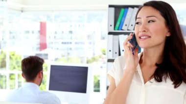 Woman talking on phone while colleague works behind her — 图库视频影像