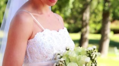 Bride holding a bouquet in the park — Stock Video
