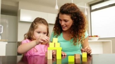 Mother and daughter playing with building blocks at the table — Stock Video