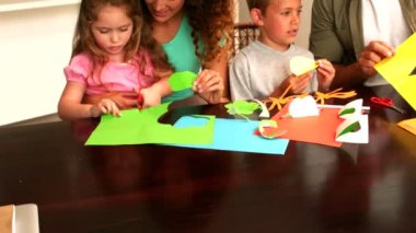 Parents and children making paper shapes together at the table — Stock Video
