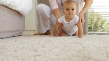 Mother helping her baby girl crawl away on the rug — Stock Video