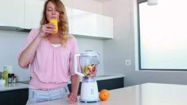 Woman in kitchen drinking orange juice beside juicer — Stock Video