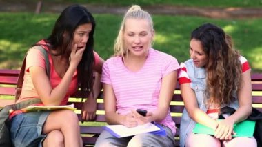 Students chatting together outside on a bench — Stock Video