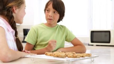 Siblings eating hot cookies from the cooling rack — Stock Video