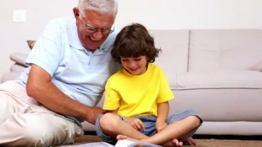 Senior man sitting on floor with his grandson looking at photo album — Stock Video