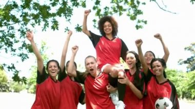 Female football team celebrating a win in the park — Stock Video