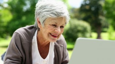 Senior woman relaxing in the park using her laptop — Stock Video