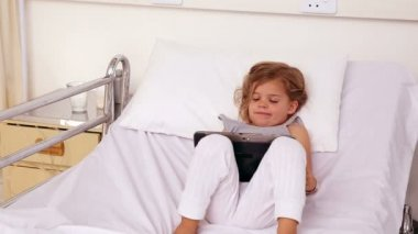 Little girl lying in hospital bed using a tablet — Stock Video
