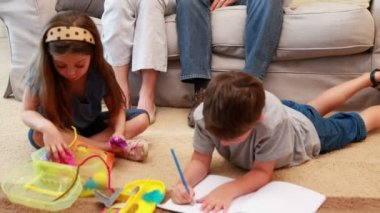 Siblings doing arts and crafts on the rug while parents look on — Stock Video