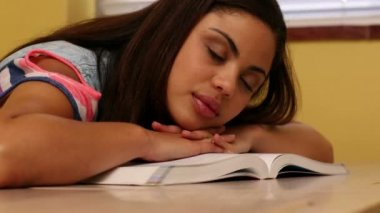 Pretty student sleeping at desk in classroom — Vídeo de stock