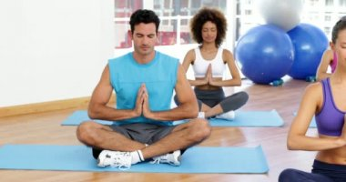 Yoga class sitting in lotus pose together — Vídeo de Stock