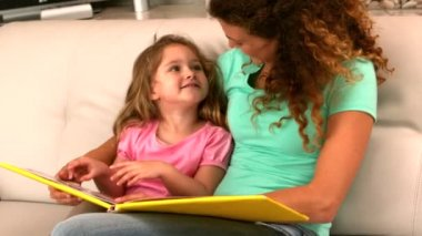 Mother and daughter reading book on the couch — Stock Video