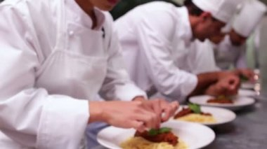 Chefs garnishing spaghetti dishes with basil leaf — Stock Video