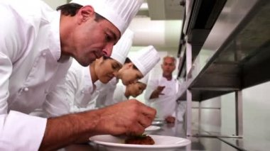 Head chef supervising his team garnishing plates — Vídeo de stock