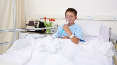 Little sick boy sitting in bed with oxygen mask — 图库视频影像