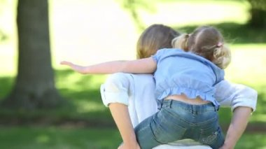 Girl getting a piggy back from mother in the park — Stock Video