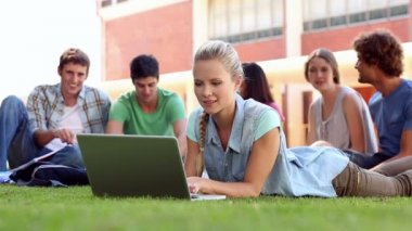 Blonde student using laptop with classmates sitting behind on grass — Stock Video