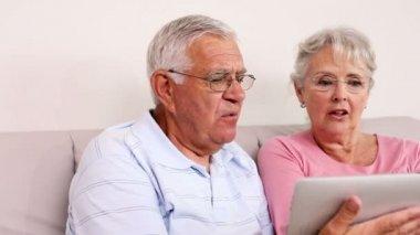 Senior couple sitting on sofa using tablet pc — Stock Video