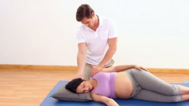 Physiotherapist massaging his pregnant patients neck — Stock Video