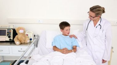 Little sick boy sitting in bed talking with doctor — Stock Video
