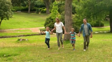 Happy family skipping in the park — Stok video