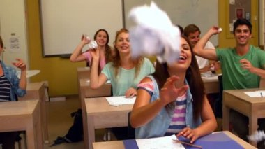 Laughing students throwing paper in classroom — Stock Video