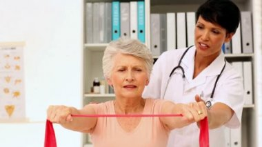 Nurse showing elderly patient how to use resistance band — Stock Video