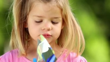 Little girl playing with pinwheel in the park — Stock Video
