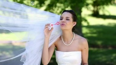 Beautiful bride blowing bubbles in the park — Stockvideo