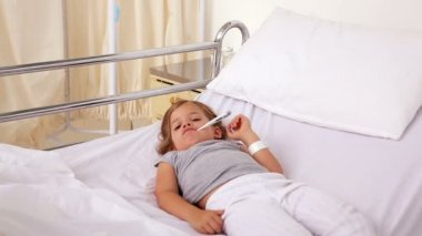 Little girl lying in hospital bed with a thermometer — Stock Video