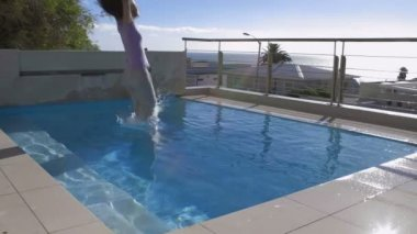 Woman jumping into pool fully clothed — Stock Video