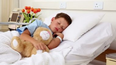 Little sick boy sleeping in bed with teddy bear — Stockvideo