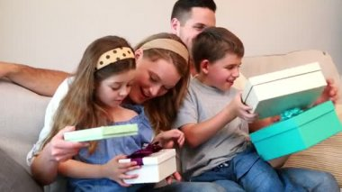 Happy young family sitting on sofa with birthday presents — Stock Video