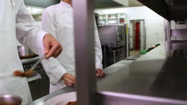 Chef en servant de spaghetti et une autre de garnir avec une feuille de basilic — Vidéo